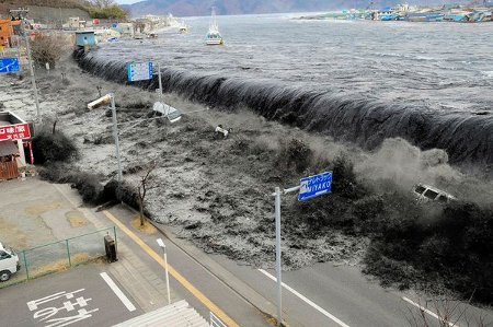 Photograph by Mainichi Shimbun, Reuters. A tsunami wave crashes over a street in Miyako City, Iwate Prefecture, in northeastern Japan on March 11.